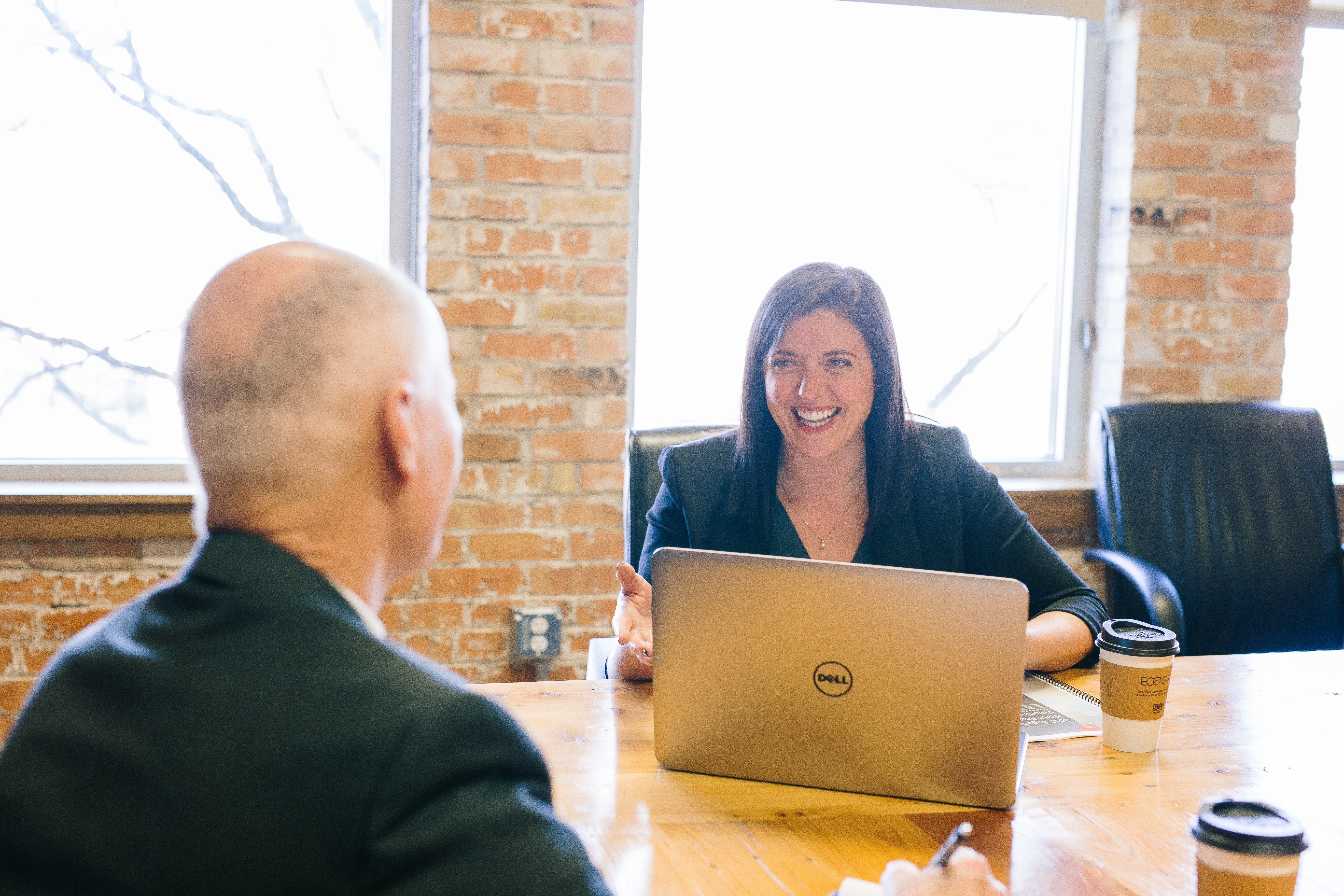 Business woman smiling at business man over board table